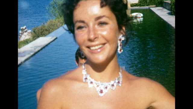 close up elizabeth taylor showing off jeweled earrings and necklace / kissing mike todd - halskette stock-videos und b-roll-filmmaterial