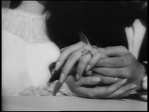 vídeos de stock, filmes e b-roll de b/w 1967 close up elvis' hand holding priscilla's with wedding ring on it / las vegas / newsreel - aliança de casamento