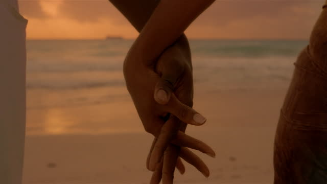 stockvideo's en b-roll-footage met close up entertwined fingers of man + woman holding hands - hand