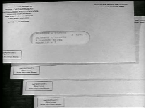 stockvideo's en b-roll-footage met b/w 1944 close up envelope with war bonds / world war ii / newsreel - kleine groep dingen