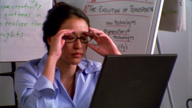 Close up exasperated woman pausing while working at laptop computer in office