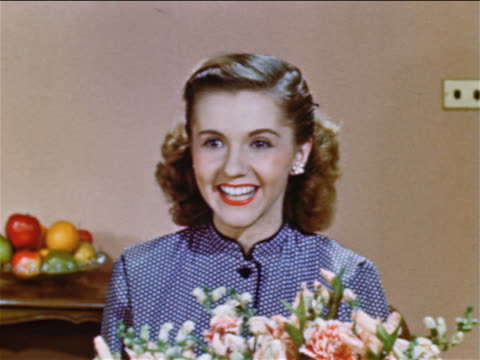 1952 close up excited teen girl sitting behind flowers talking to someone off screen / industrial - 1952 stock videos & royalty-free footage