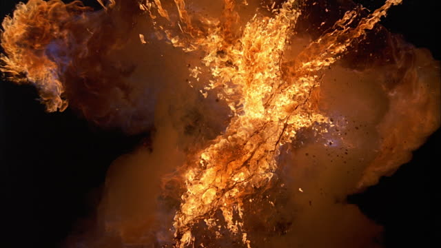 vídeos de stock e filmes b-roll de close up explosion against black backdrop / flammable liquid spraying out from flames - incêndio