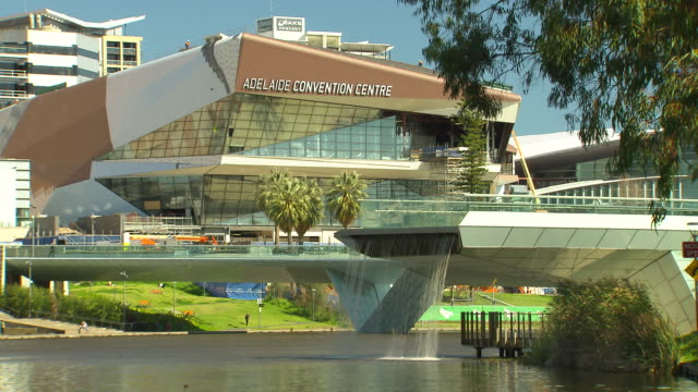 close up exterior adelaide convention centre / torrens river, with a man made water fall cascading from the torrens river footbridge. adelaide... - adelaide river stock videos & royalty-free footage