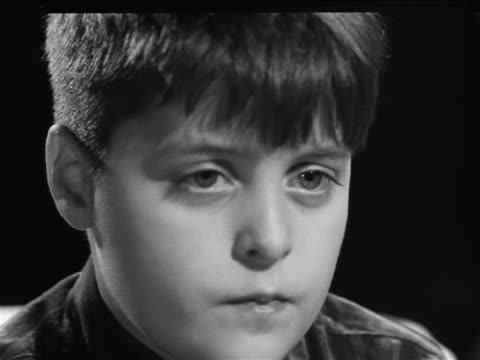 b/w 1961 close up face of bored boy with braces eating + looking offscreen (watching tv) / documentary - brace stock videos and b-roll footage