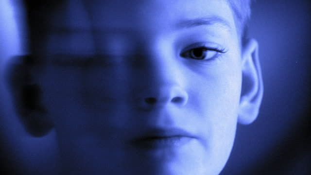 Close up face of boy with projection of blue light and question marks over face
