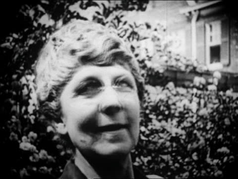 b/w 1920 close up face of florence harding in eyeglasses looking at camera outdoors / newsreel - solo una donna matura video stock e b–roll