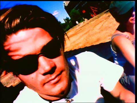 close up face of generation x man in sunglasses looking at camera outdoors - x世代点の映像素材/bロール
