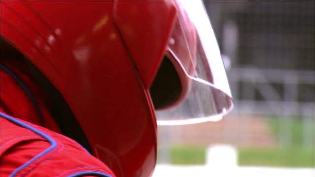close up face of man wearing helmet turning around and looking at cam - helm stock-videos und b-roll-filmmaterial