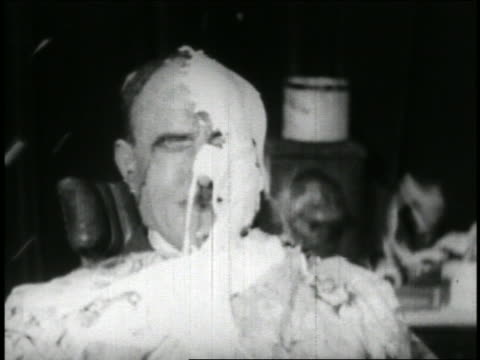 b/w 1928 close up face of seated middle-aged man getting food thrown into face / short - 1928 stock videos & royalty-free footage
