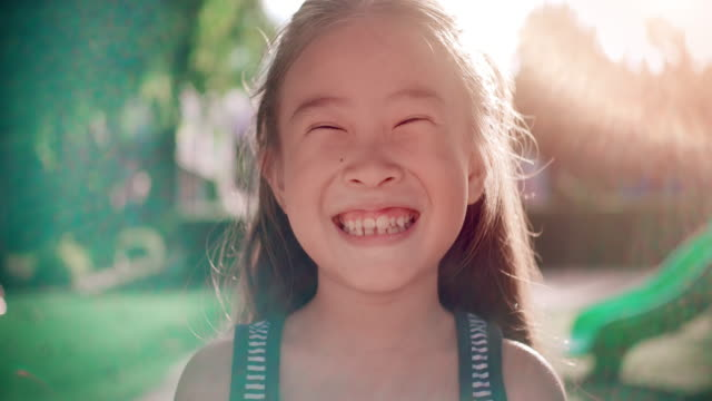 slo mo close up face of smile happy asian girl - smiling stock videos & royalty-free footage