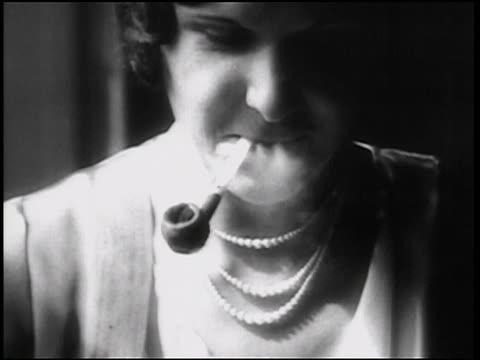 b/w 1938 close up face of woman smoking pipe + looking down / newsreel - ボング点の映像素材/bロール