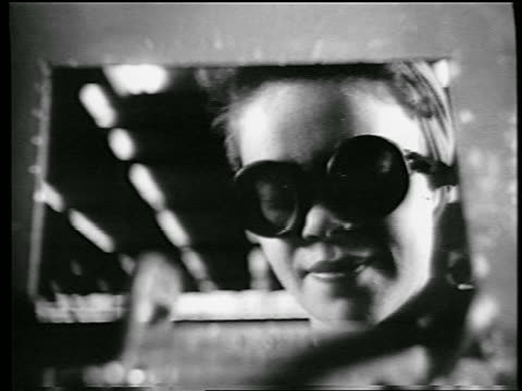vidéos et rushes de b/w 1944 close up face of woman with goggles kerchief on head riveting in defense plant / removes goggles - world war 1