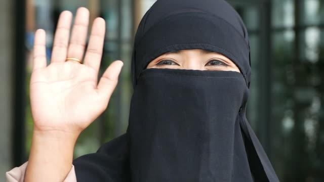 vídeos y material grabado en eventos de stock de close up face joven mujer musulmana asiática , hola adiós y haciendo señas de gesticada - sólo una adolescente