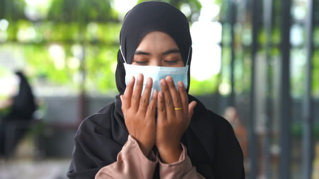 close up face young asian muslim woman with  surgical mask protection , praying and prostrating , praying namaj time - malaysia stock videos & royalty-free footage
