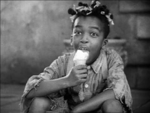 b/w 1931 close up farina from our gang sitting outdoors eating ice cream cone / feature - 1931 stock videos & royalty-free footage