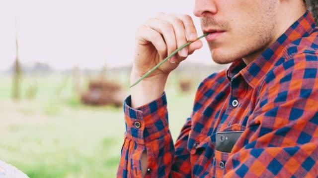 vidéos et rushes de bouchent agriculteur chewing herbe et cracher, temps réel - mâcher