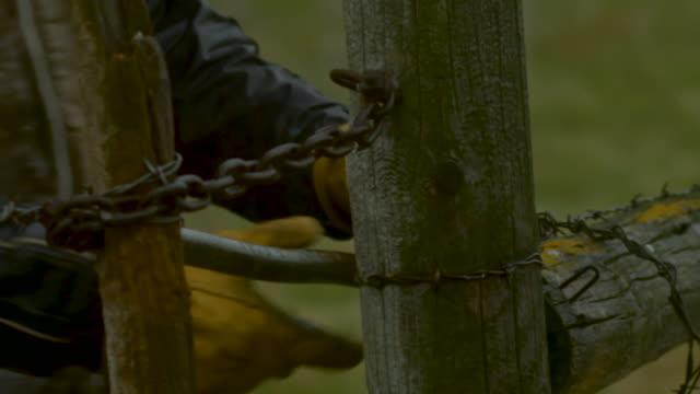 Close Up Farmer's Hands unlocking Fence