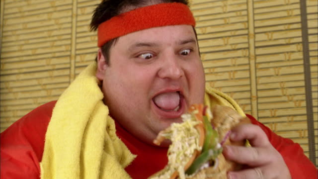 Close up fat man eating messy sandwich excitedly