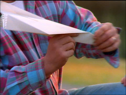 close up father helping son fly paper airplane outdoors
