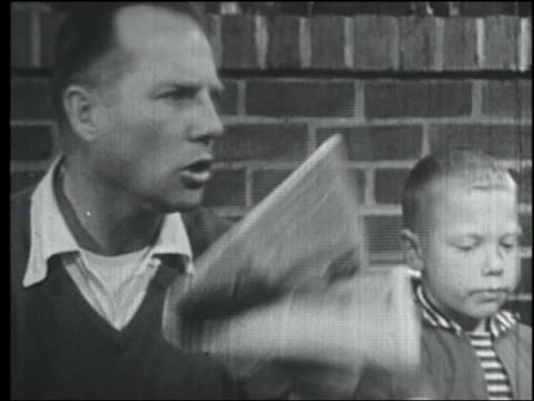b/w 1958 close up father + son looking up from paper at breakfast + get up from table - 1950 stock videos & royalty-free footage