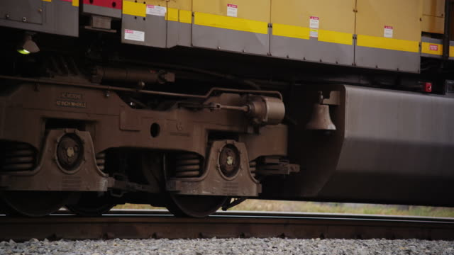 Close up featuring the wheels of a train engine rolling down the track, coming to a stop.