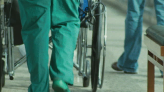 close up feet and legs of a nurse wearing hospital scrubs walking away from camera pushing a patient in a wheelchair. - scrubs stock-videos und b-roll-filmmaterial