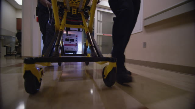 Close up feet and legs of emergency medical technicians pulling a gurney with an emergency trauma patient down the hallway of a hospital ER.