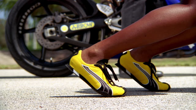 Close up feet of female runner in starting position wearing track shoes / motorcycle in background