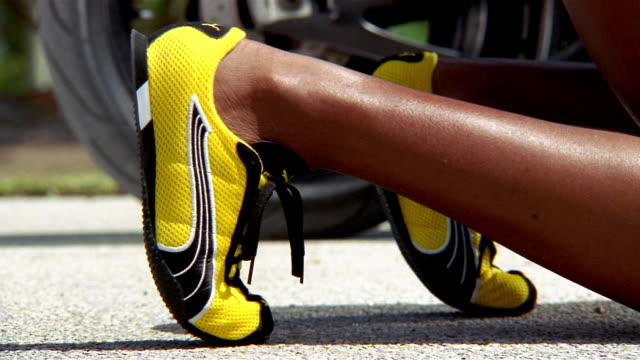 Close up feet of female runner in starting position wearing track shoes