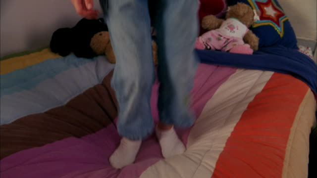 close up feet of girl jumping up and down on bed - socke stock-videos und b-roll-filmmaterial