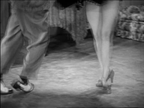 vidéos et rushes de b/w 1946 close up feet of patty lacey & ray hirsch dancing wildly on carpet / short film - rock