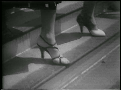 b/w 1953 close up feet of women in high heel shoes walking down stairs outdoors / newsreel - high heels stock videos & royalty-free footage
