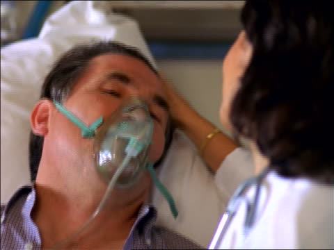 close up female doctor stroking forehead of middle-aged male patient with oxygen mask in hospital - oxygen mask stock videos & royalty-free footage