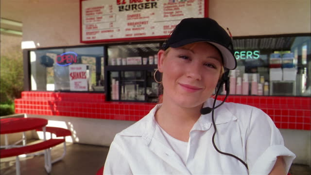 close up female fast food restaurant employee w/headset smiling at cam outside restaurant - first job stock videos & royalty-free footage