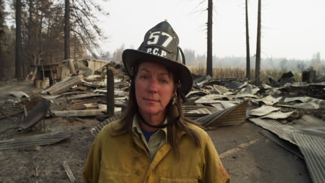 vídeos de stock e filmes b-roll de close up, female firefighter stands in front of wildfire destruction - bombeiro
