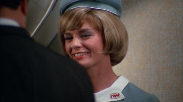1966 close up female flight attendant smiling and saying goodbye to passengers exiting plane - twa video stock e b–roll