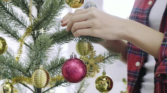 間近で女性の手は、クリスマス パーティーを始める前に、クリスマス ツリーを飾る。 - ティンセル点の映像素材/bロール