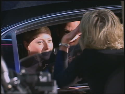 Close up female reporter talking into mic in front of limo / window rolling down / famous couple / AUDIO