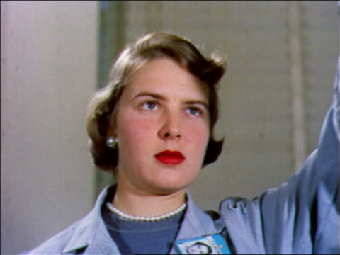 1957 close up female scientist with arm raised pouring something offscreen / bell labs - 1957 video stock e b–roll