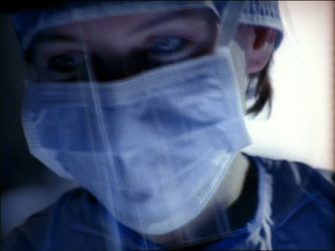 close up female surgeon in operating room dressed in surgical clothing, mask and plastic face shield - operating stock videos & royalty-free footage