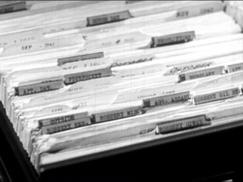 stockvideo's en b-roll-footage met 1947 close up file cabinet drawer opening up and hands flipping through files/ dearborn, michigan - rapport