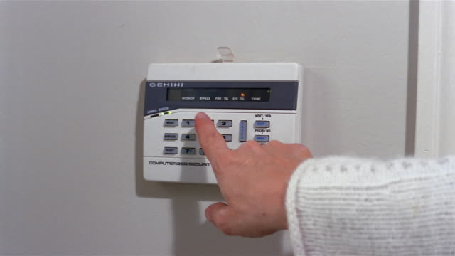 Close up finger entering code on keypad / setting home burglar alarm