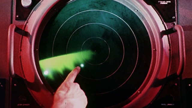 Close up finger pointing at signals displayed on circular radar screen with revolving green wave