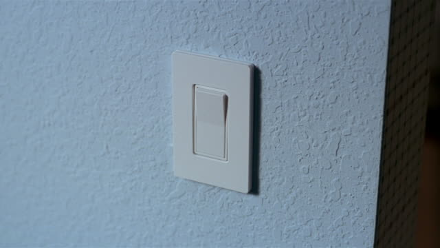 vídeos de stock, filmes e b-roll de close up finger pressing flat light switch and  turning on light / switching off light - interruptor de luz