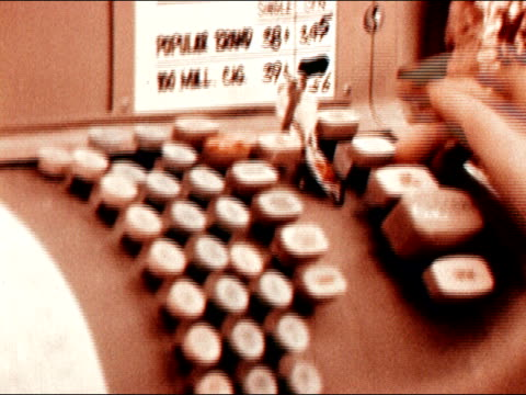 1971 close up fingers pushing keys on cash register/ zoom out medium shot young woman working as cashier/ california/ audio - 1971年点の映像素材/bロール