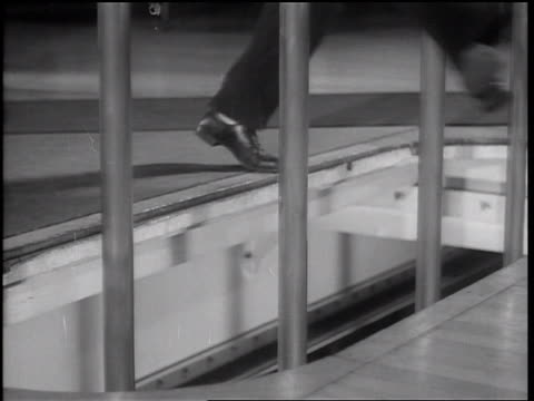 b/w 1936 close up fireman + cat jumping + sliding down poles through floor - rutschen stock-videos und b-roll-filmmaterial