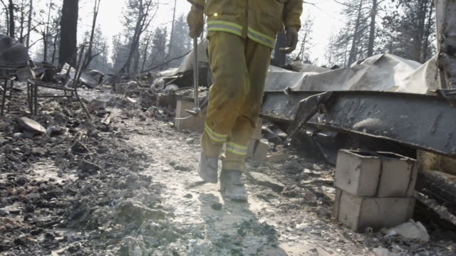 close up, fireman walks through wildfire rubble - natural disaster stock videos & royalty-free footage