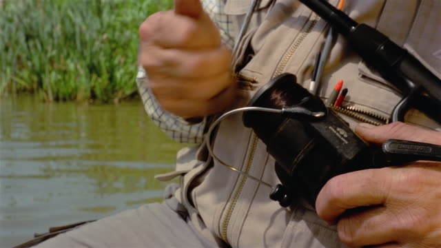 close up fisherman's hands winding fishing line onto reel / pan to water - fishing line stock videos & royalty-free footage
