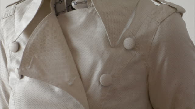 close up fitting trenchcoat on model - adjusting stock videos and b-roll footage
